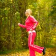 Young woman running in autumn fall forest park — Stock Photo