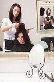 Curly woman looking at mirror by hairstylist. In hairdressing salon. — Stock Photo