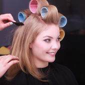 Blond girl hair curlers rollers by hairdresser in hairdressing salon — Stock Photo