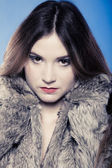 Portrait of girl with long hair. Young woman in fur coat on blue. — Stock Photo
