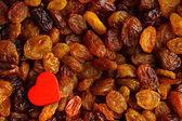 Kost hälsosam mat. russin som bakgrund konsistens och rött hjärta — Stockfoto