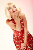 Pinup girl in blond wig retro dress blowing a kiss — Stock Photo