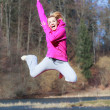 Cheerful teenage girl in pink tracksuit jumping outdoor — Stock Photo #45797251