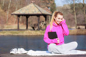 Teenage girl in tracksuit using tablet on pier outdoor — Stock Photo