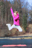 Cheerful teenage girl in pink tracksuit jumping outdoor — Stock Photo
