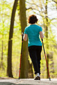 Nordic walking. Woman hiking in the forest park. — Foto de Stock
