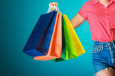 Colorful shopping bags in female hand. — Stock Photo