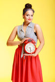 Portrait of fashionable pin-up girl holding red clock — Stock Photo