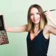 Woman applying eyeshadow with makeup palette — Stock Photo #46369161