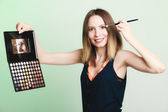 Woman applying eyeshadow with makeup palette — Stock Photo
