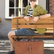 Young handsome man with suitcase waits on bench — Stock Photo #46571333