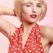 Pinup girl in blond wig and retro red dress winking. — Stock Photo #46571407