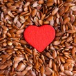 Flax seeds linseed as food background and red heart — Stock Photo