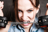 Criminal woman prisoner biting handcuffs — Stock Photo