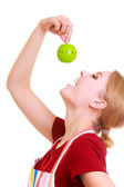 Funny housewife in kitchen apron trying to eat apple timer isolated — Stock Photo