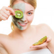 Woman in clay mask on face covering eye with kiwi — Stock Photo #47046995