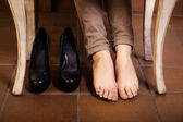 Bare female feet under the vintage table. — Stock Photo