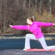Teenage girl in tracksuit doing exercise on pier outdoor — Stock Photo #47520905