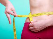 Ragazza fitness con nastro di misura misura la sua vita — Zdjęcie stockowe