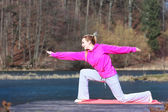 Teenage girl in tracksuit doing exercise on pier outdoor — Stock Photo
