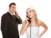 Angry bride and groom talking on phone — Stock Photo