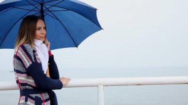 Kvinna med ett paraply skickar en luft kyss — Stockvideo