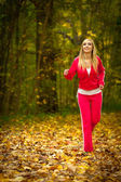 Blonde young woman running jogging in autumn fall forest park — Stock Photo