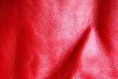 Texture of folds vivid red skin leather background — Stock Photo