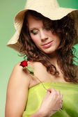 Young woman in hat holding red rose flower — Stock Photo