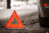 Red warning triangle sign on road — Стоковое фото