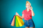 Pinup girl with shopping bags calling on phone — Stock Photo