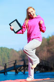 Teenage girl in pink tracksuit showing blank tablet outdoor — Stock Photo