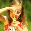 Child blowing a soap bubbles on the meadow or in the park. — Stock Video