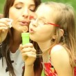 Young woman and girl blowing a soap bubbles — Stock Video