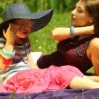 Mother  with little daughter in straw hat and eyeglasses relaxing on the meadow or in the park. — Stock Video #48015599
