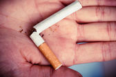 Broken cigarette on hand. — Stock Photo
