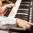 Boy playing on digital keyboard piano synthesizer — Stock Photo #48578975