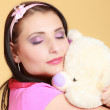 Childish young woman in pink hugging teddy bear toy — Stock Photo