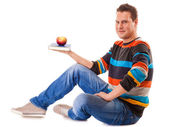 Man holding book and red apple — Stock Photo