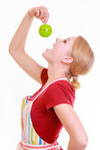 Funny housewife in kitchen apron trying to eat apple timer — Stock Photo