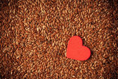 Flax seeds linseed as food background and red heart — Stok fotoğraf