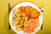 Fried chicken roasted potatos and carrot salad. — Stock Photo