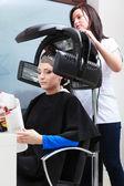 Woman dying hair reading magazine — Stock Photo