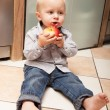 Little child eating apple fruit at home — Stock Photo