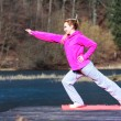 Teenage girl in tracksuit doing exercise on pier outdoor — Stock Photo #48822373