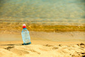 Bottle of water drink on a sandy beach. — Stock Photo
