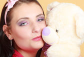 Childish young woman  in pink kissing teddy bear toy — Stock Photo
