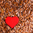 Flax seeds linseed as food background and red heart — Stock Photo #49240495