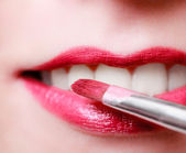 Closeup female red pink lips with makeup lipstick brush — Stock Photo