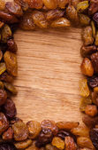 Border of raisin on wooden background — Stock Photo